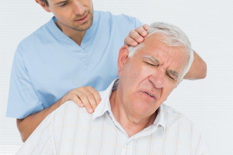 Quiroprático masculino que faz o ajuste do pescoço foto de stock