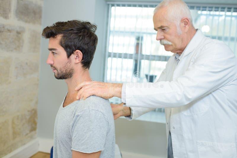 Quiroprático masculino que faz o ajuste do pescoço no centro de reabilitação fotos de stock royalty free