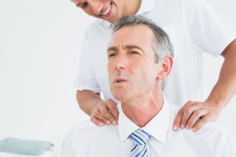 Quiroprático que faz massagens o pescoço dos pacientes imagens de stock royalty free