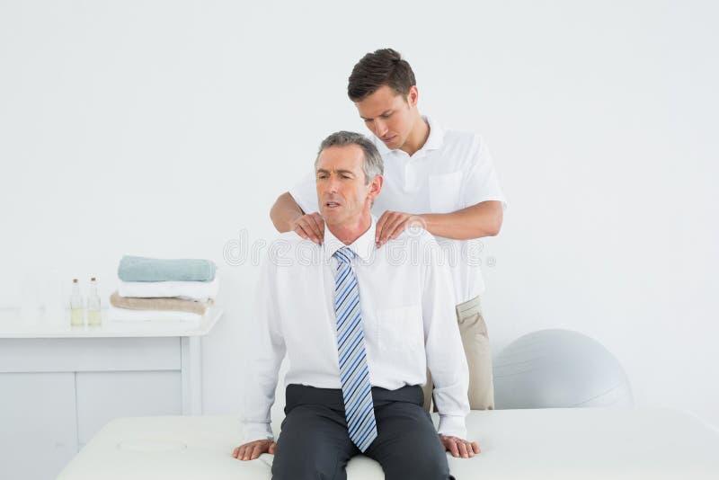 Quiroprático que faz massagens um ombro maduro dos pacientes fotografia de stock
