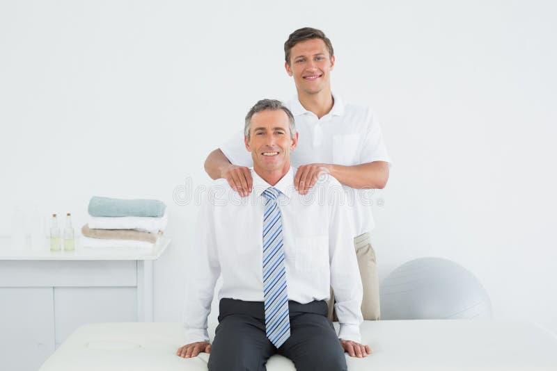 Quiroprático que faz massagens um ombro maduro dos pacientes imagens de stock royalty free