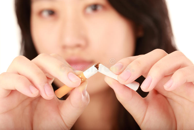 Quit smoking. Woman with a broken cigarette stock images