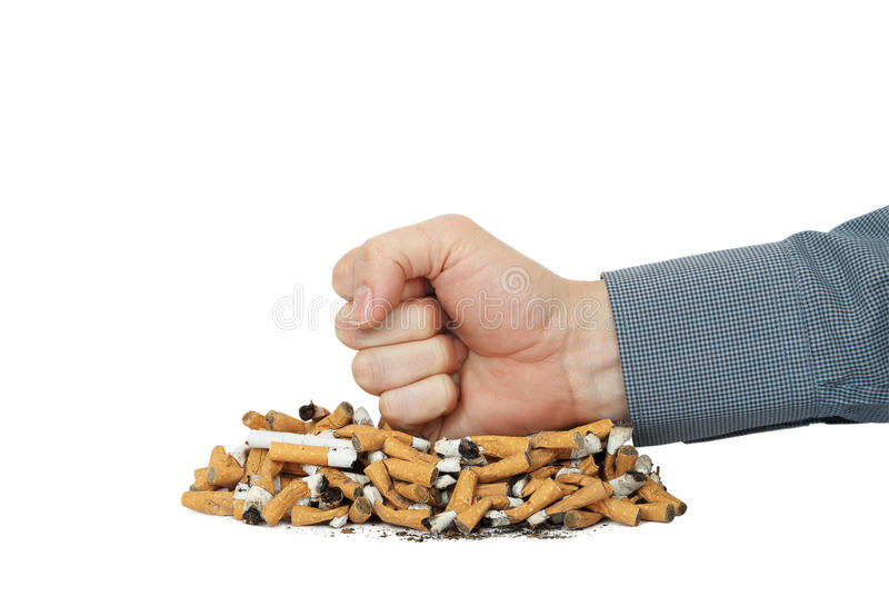 Quit smoking. Smoker's fist on heap of cigarettes stock photography