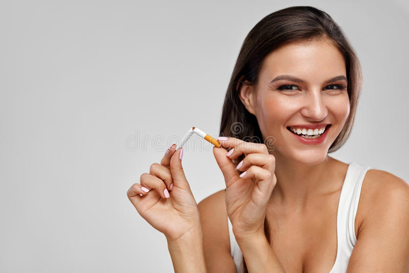 Quit Smoking. Beautiful Happy Woman Holding Broken Cigarette. Quit Smoking Cigarettes. Portrait Of Beautiful Smiling Woman Quitting Smoking By Breaking Cigarette stock images