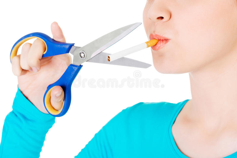 Quit smoking. Woman cutting cigarette with scissors royalty free stock images