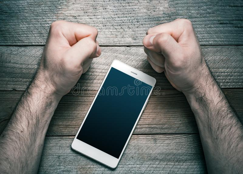 Quit Using Smartphone Or Social Media Concept With A White Mobile Phone Surrounded By 2 Stressed Looking Clenched Fists royalty free stock photos