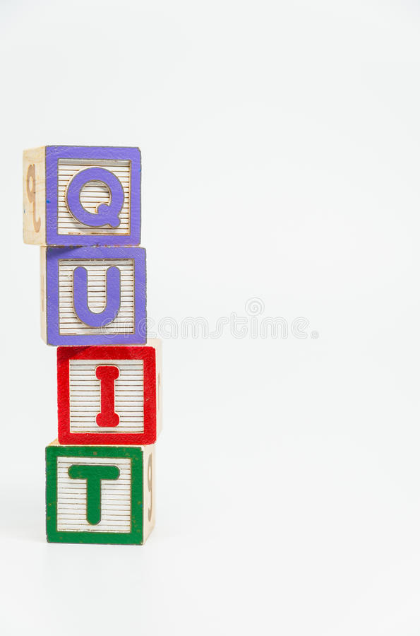 QUIT word wooden block arrange in vertical style on white background and selective focus. 1 stock photography