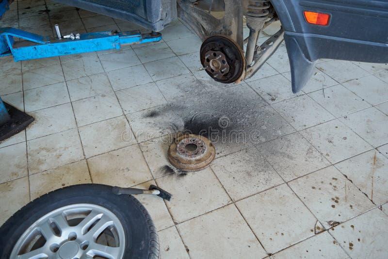Quitando y comprobando el tambor de freno en la rueda posterior del coche fotografía de archivo