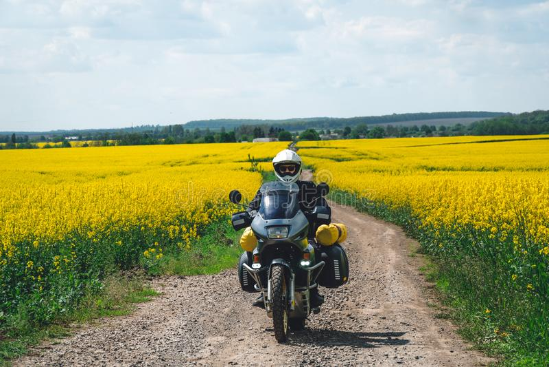 ?quitation extr?me de sport d'homme voyageant la moto d'enduro sur la salet? beau champ jaune des fleurs Cavalier d'aventure du m photos libres de droits