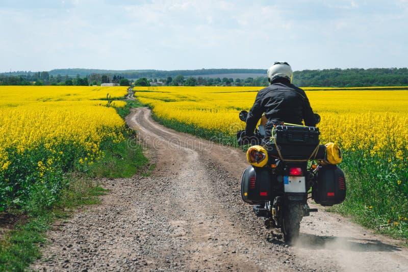 ?quitation extr?me de sport d'homme voyageant la moto d'enduro sur la salet? beau champ jaune des fleurs Cavalier d'aventure du m image stock