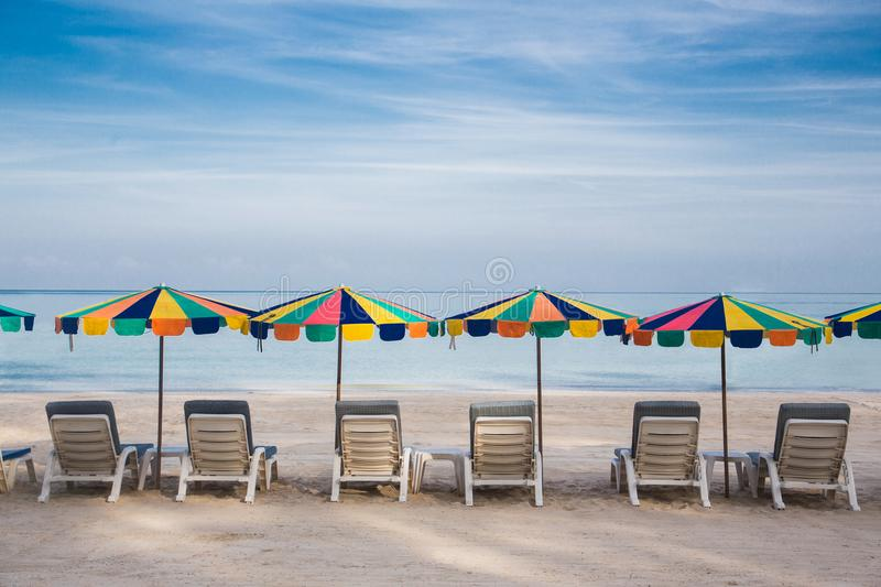 Quite beach with umbrellas and beach chairs and clear blue sky. royalty free stock photography