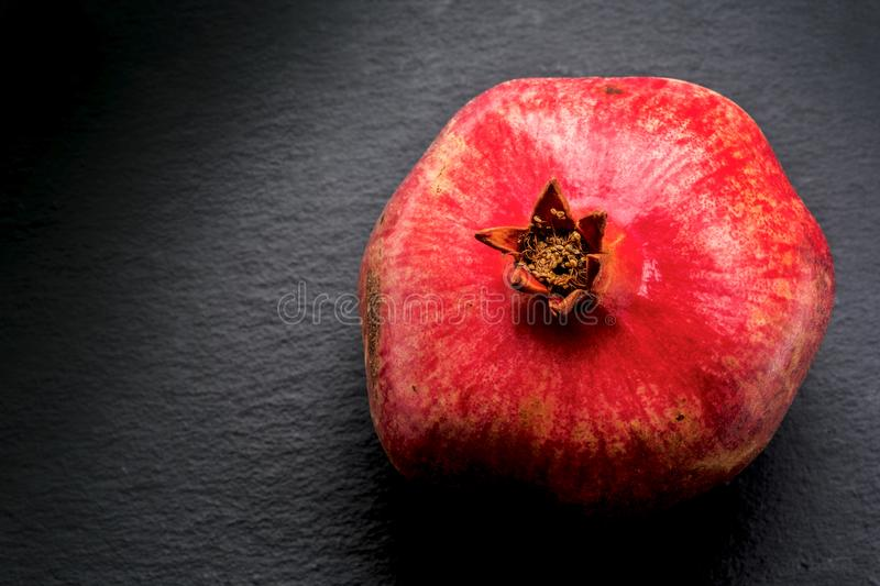 Ruby red pomegranate on shale stock image