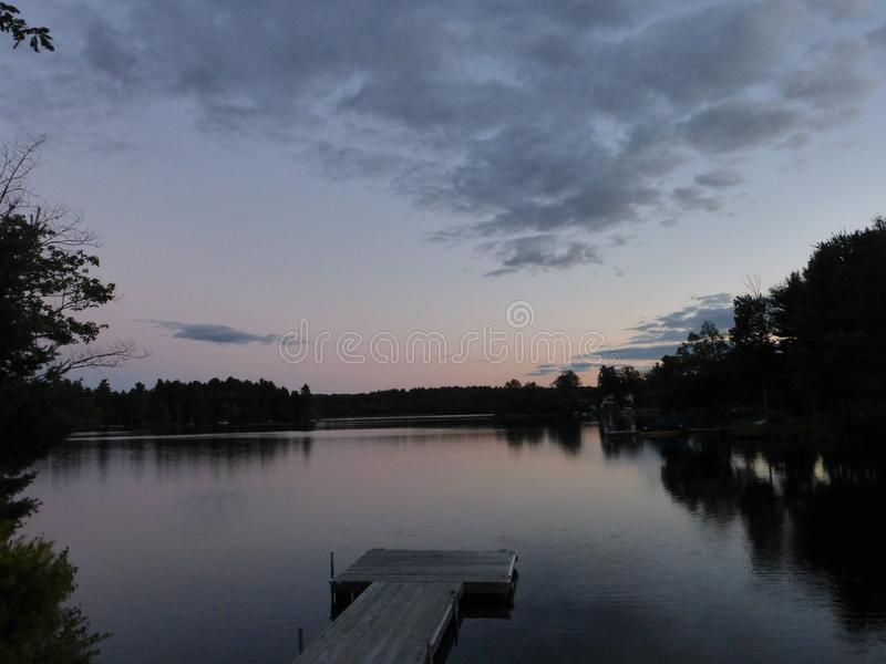 Dusk on a lake with a dock. Quite time on a lake with suttle colors and unique cloud formation creating a somber end to a beautiful day royalty free stock images