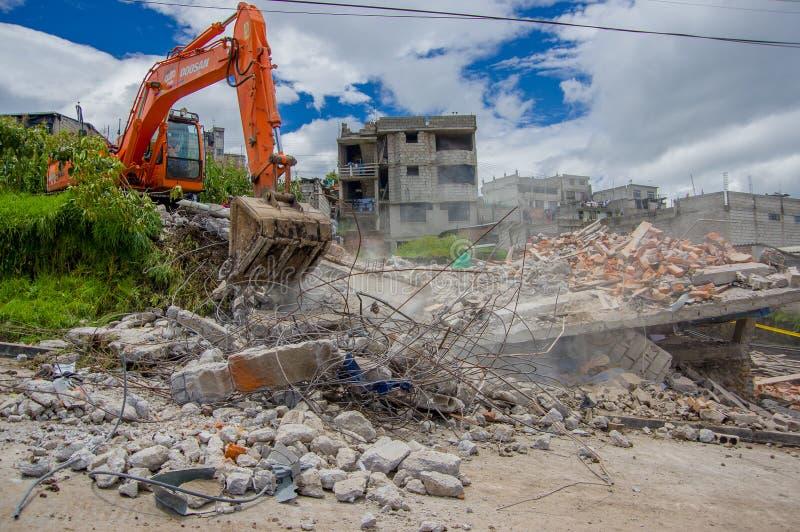 Quito, Ecuador - abril, 17, 2016: Casa destruida por terremoto, y maquinaria pesada que limpia el desastre en la ciudad de Quito, fotografía de archivo