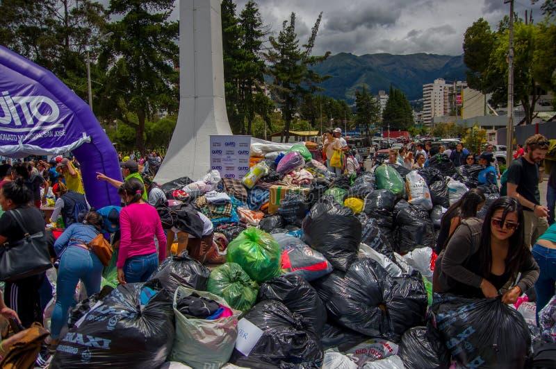 Quito, Ecuador - April, 17, 2016: Niet geïdentificeerde burgers die van Quito hulp bij rampenvoedsel, kleren, geneeskunde en wate stock fotografie