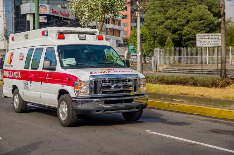 QUITO, ECUADOR - 7 DE JULIO DE 2015: Vadee la ambulancia blanca con los detalles rojos que cruzan la ciudad, emergencias solament foto de archivo