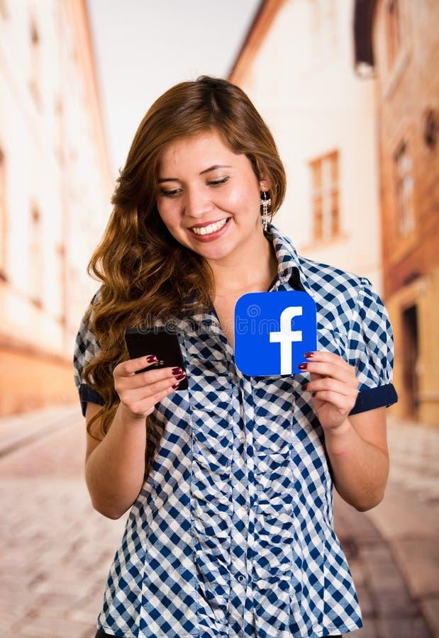 Quito, Ecuador - 11 de marzo de 2016: Mujer joven sonriente con el teléfono móvil moderno en las manos que llevan a cabo un icono imagenes de archivo
