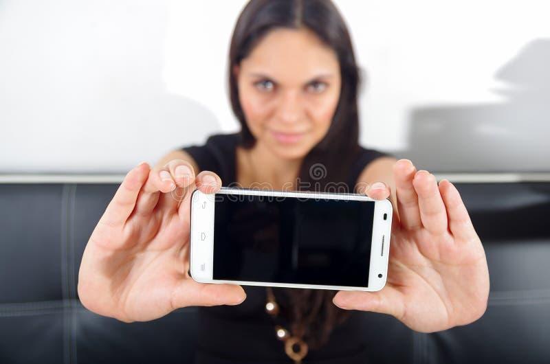 Quito, Ecuador - 9 de mayo de 2017: Mujer hermosa que sostiene un teléfono móvil moderno usando señalar adentro de ella en Apple fotos de archivo