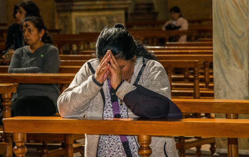QUITO, ECUADOR, FEBRUARY 22, 2018: Indoor view of unidentified people praying inside of la Catedral church in Quito`s. Cathedral royalty free stock photography