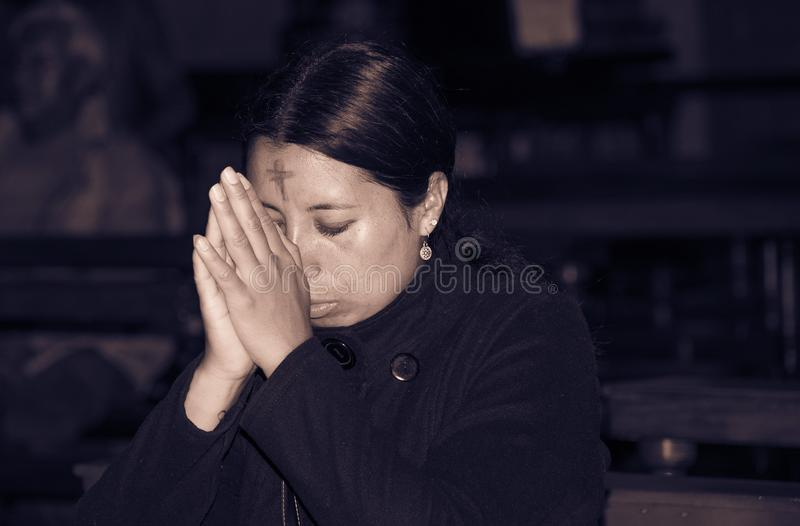 QUITO, ECUADOR, FEBRUARY 22, 2018: Indoor view of unidentified people praying inside of la Catedral church in Quito`s. Cathedral stock photography