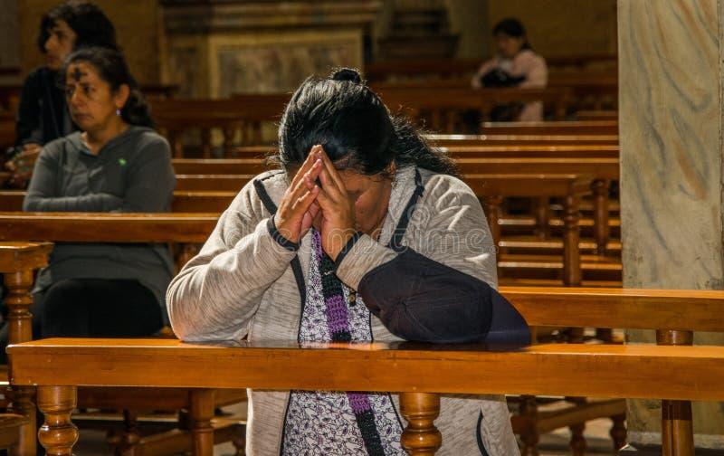 QUITO, ECUADOR, IL 22 FEBBRAIO 2018: Punto di vista dell'interno della gente non identificata che prega dentro della chiesa di Ca fotografia stock libera da diritti