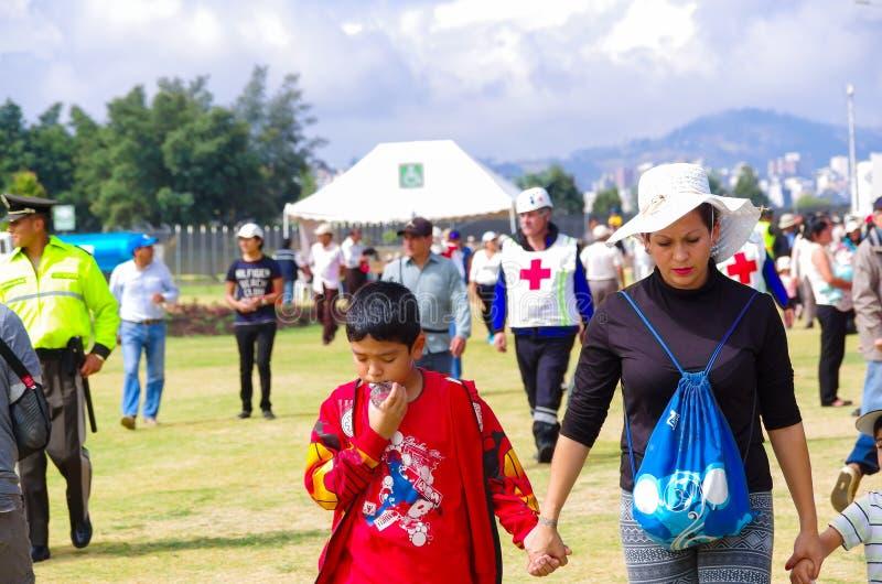 QUITO, ECUADOR - JULI 7, 2015: Selectieve nadruk voor een vrouw met een witte hoed en zijn zoon in haar hand Eerste hulpen en royalty-vrije stock foto's