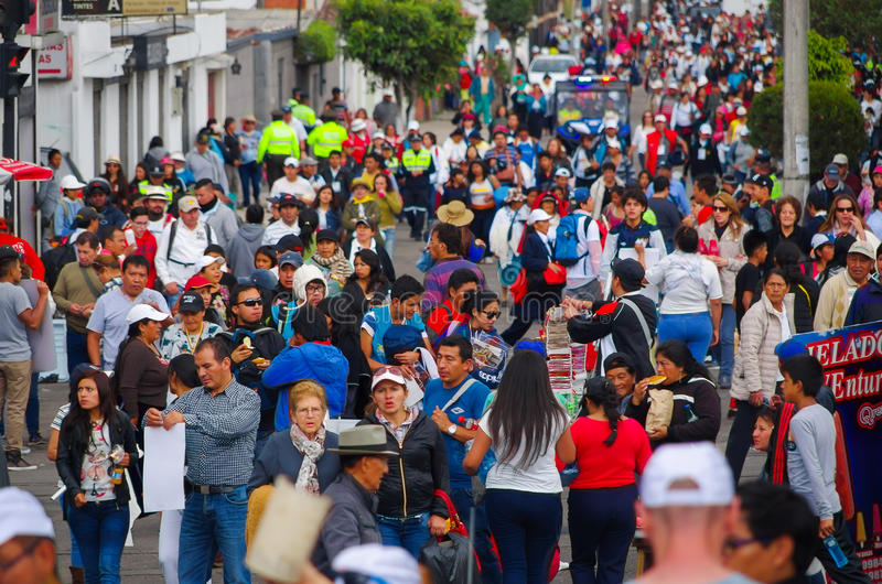 QUITO, ECUADOR - JULY 7, 2015: Crowded avenue with lots of people walking, police watching and guarding people.  royalty free stock photography
