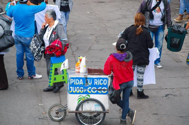 QUITO, ECUADOR - 7 LUGLIO 2015: Donna dal succo di vendita posteriore della noce di cocco, stante in mezzo alla via fotografie stock