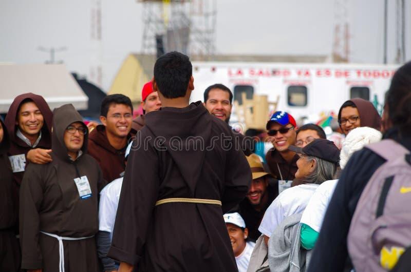 QUITO, ECUADOR - 7 LUGLIO 2015: Nell'evento della massa di papa, gruppo dei sacerdoti con la gente che prova ad ottenere una foto immagini stock libere da diritti