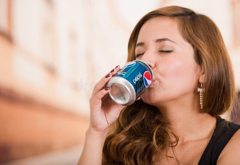 Quito, Ecuador - 6 maggio 2017: Giovane donna graziosa che beve una pepsi-cola nel fondo vago della città fotografia stock