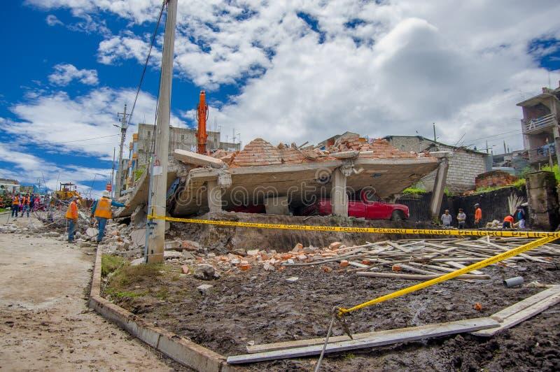 Quito Ekwador, Kwiecień, -, 17, 2016: Mieści zniszczonego trzęsieniem ziemi, z czerwonym samochodem łapiącym pod zniszczoną budow obraz stock