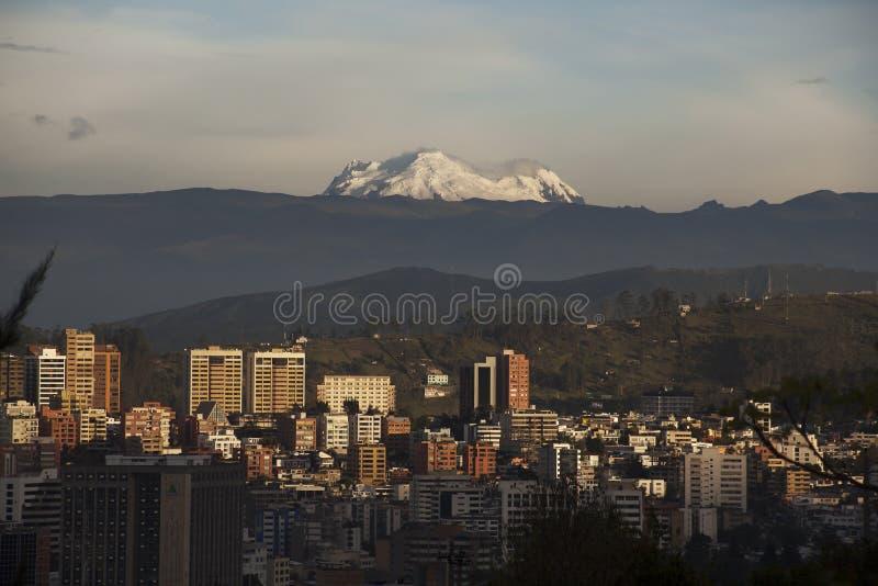 Quito en la puesta del sol con el volcán de Antisana imagenes de archivo