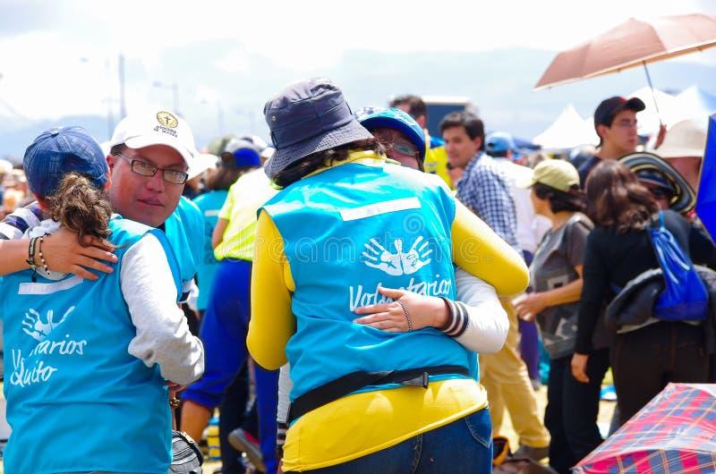 QUITO, EQUADOR - 7 DE JULHO DE 2015: Povos que dão a paz na massa do papa Francisco, voluntários em um aperto do dia ensolarado fotos de stock royalty free