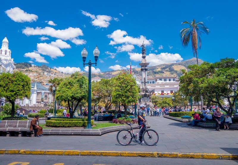 QUITO, EQUADOR - MARZO 23, 2015: Homem não identificado e seu bycicle que passam o trought que a independência esquadra em Quito, imagens de stock royalty free