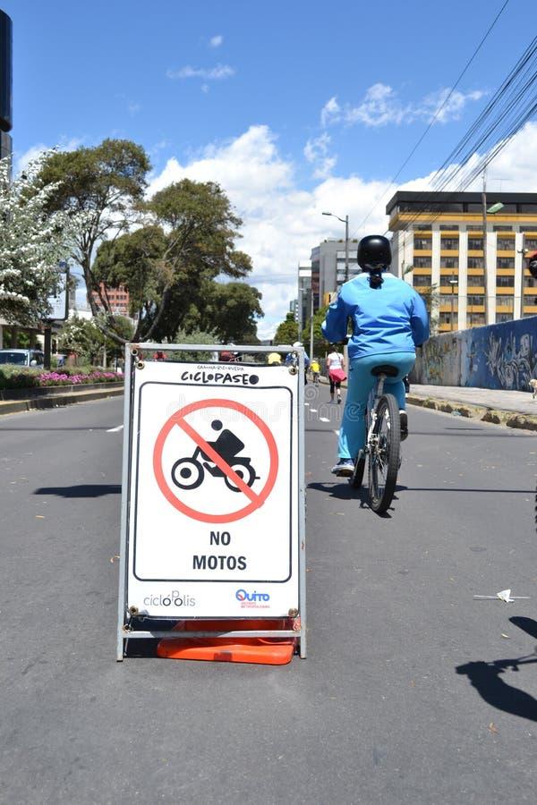 QUITO, EQUATEUR - 28 JANVIER 2016 : Jeune femme faisant du vélo dans la ville de Quito, près de elle un signal de publicité de pa image libre de droits