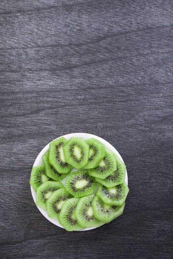 Quivi cortado fresco na placa Fatias verdes do fruto de quivi no fundo de madeira escuro imagens de stock royalty free
