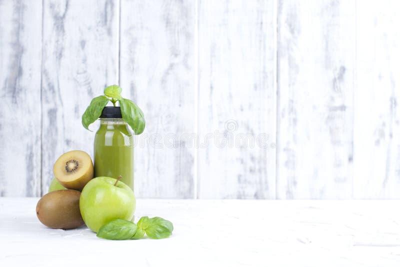 Quivi, maçã verde, manjericão e suco em uma garrafa plástica Alimento da desintoxicação Fundo de madeira branco Copie o espaço imagens de stock