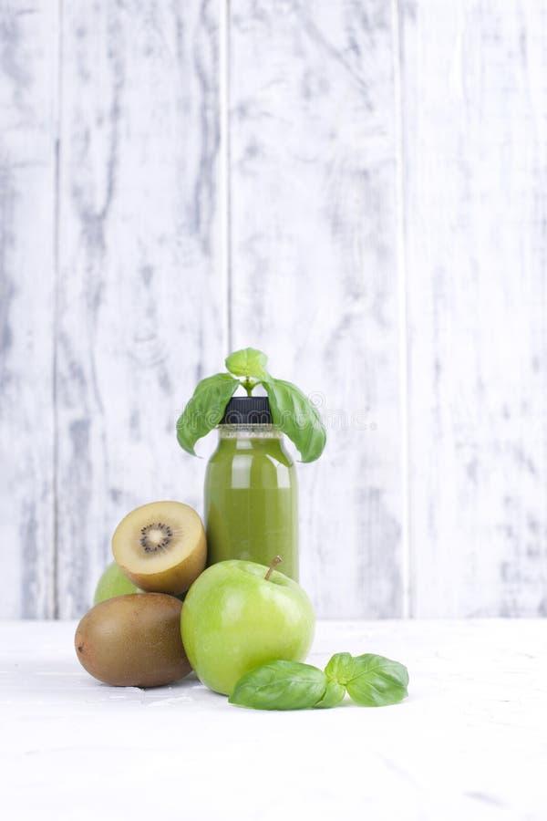 Quivi, maçã verde, manjericão e suco em uma garrafa plástica Alimento da desintoxicação Fundo de madeira branco Copie o espaço foto de stock royalty free