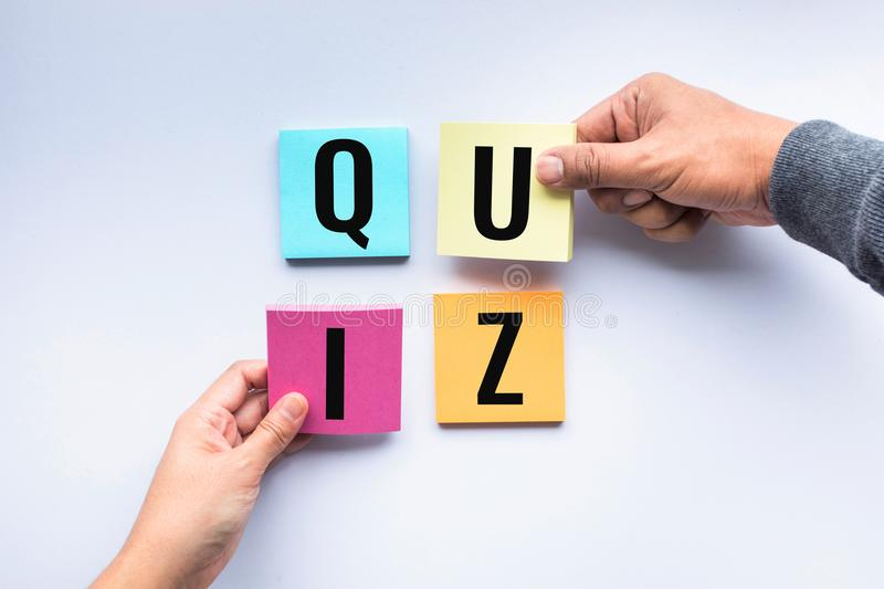 Quiz word on notepaper with hand. Quiz word on notepaper with human hand royalty free stock image