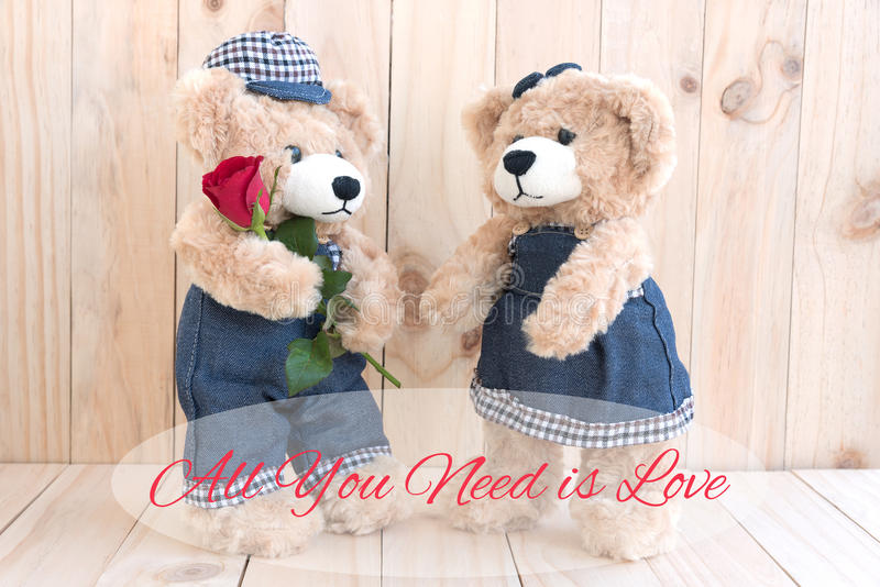 Quote all you need is love with couple teddy bear stock photo