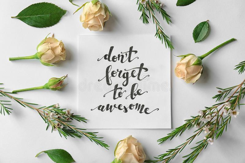 Quote `Dont forget to be awesome` written on paper with roses and leaves on white background stock photo