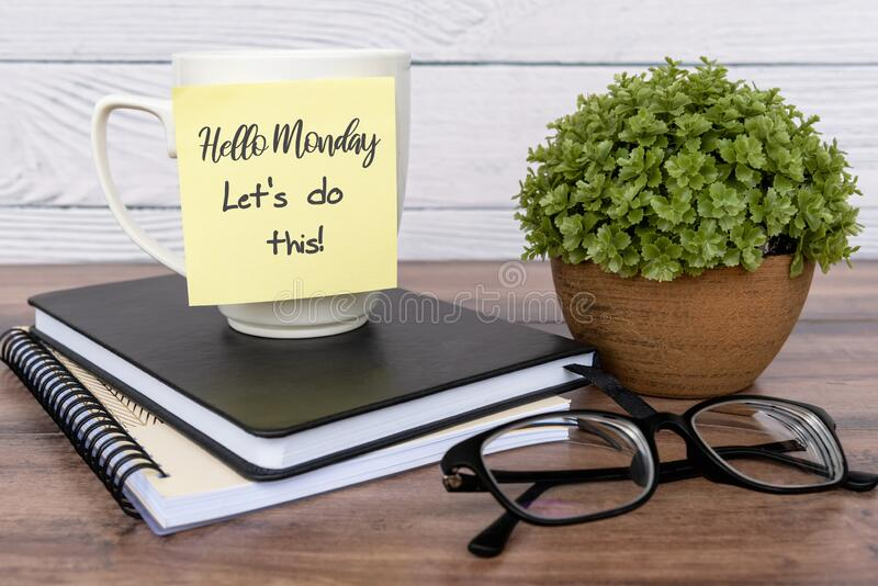 Quotes - Hello Monday, let`s do this text on sticky note on top of table. Inspirational quotes - Hello Monday, let`s do this text on sticky note on top of table royalty free stock image