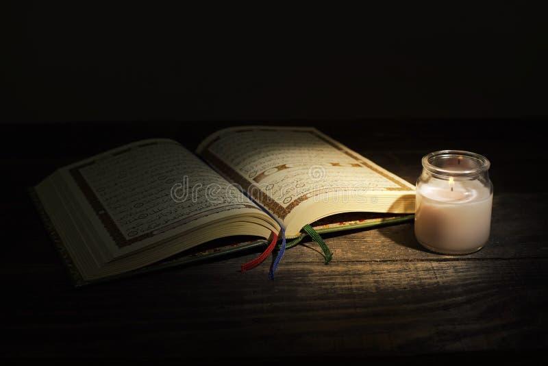 """Qur """", святая книга ислама месяц поклонению Рамазан, читая Священное Писание путем использование света свечи стоковые изображения"""