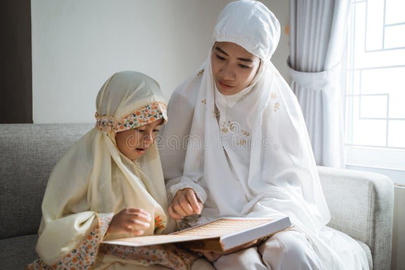 Quran da leitura da mãe e da criança foto de stock
