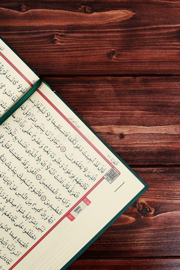 Quran islámico del libro sagrado con las gotas del rosario en fondo de madera de la tabla Kuran los musulmanes del OS del libro s imagen de archivo libre de regalías