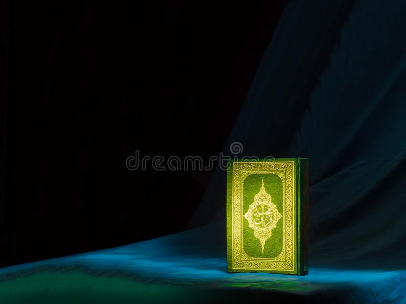 Quran, the islamic holy book. & x22;Quran& x22; or Kuran, the islamic holy book, in arabic text on dark background stock images
