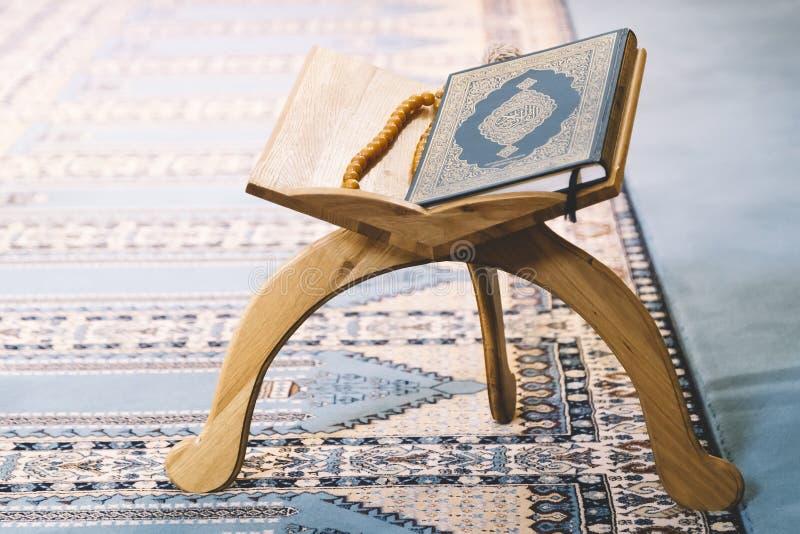 Quran, libro sagrado de musulmanes en soporte de madera fotos de archivo