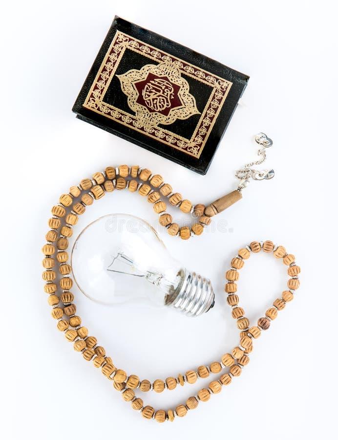 Quran mit Rosenbeet mit Lampe - Heilige Schrift von Moslems - der Koran - wei?er Hintergrund des Quran stockfotografie