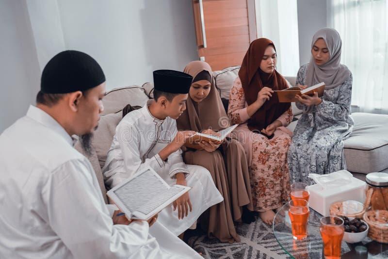 Quran muçulmano da leitura da família junto na sala de visitas imagem de stock royalty free