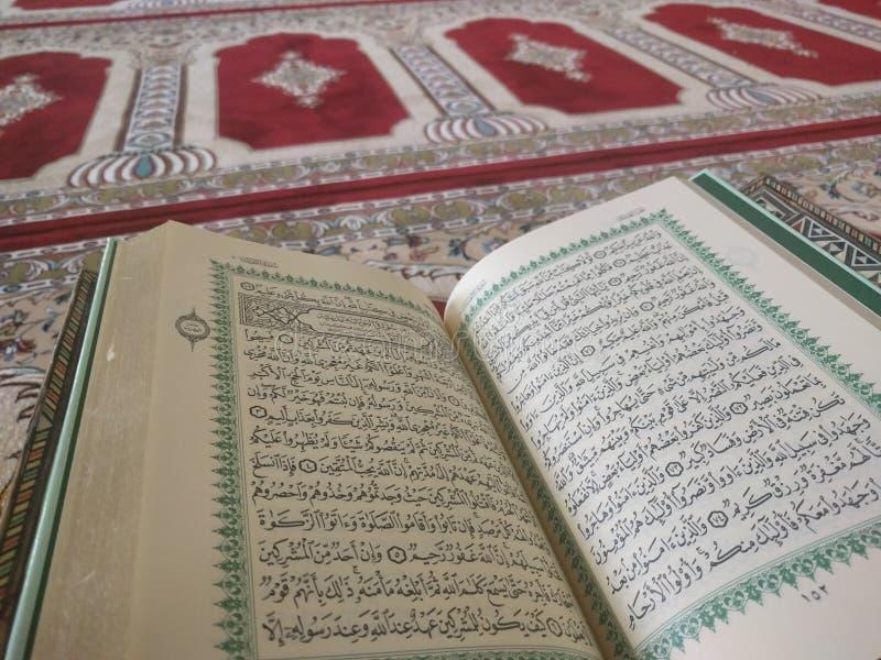 Quran på eleganta persiska filtar - den arabiska texten med engelsk översättning royaltyfri foto